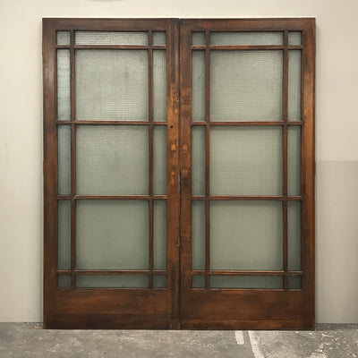 A pair of antique glazed dividing panelled doors in teak