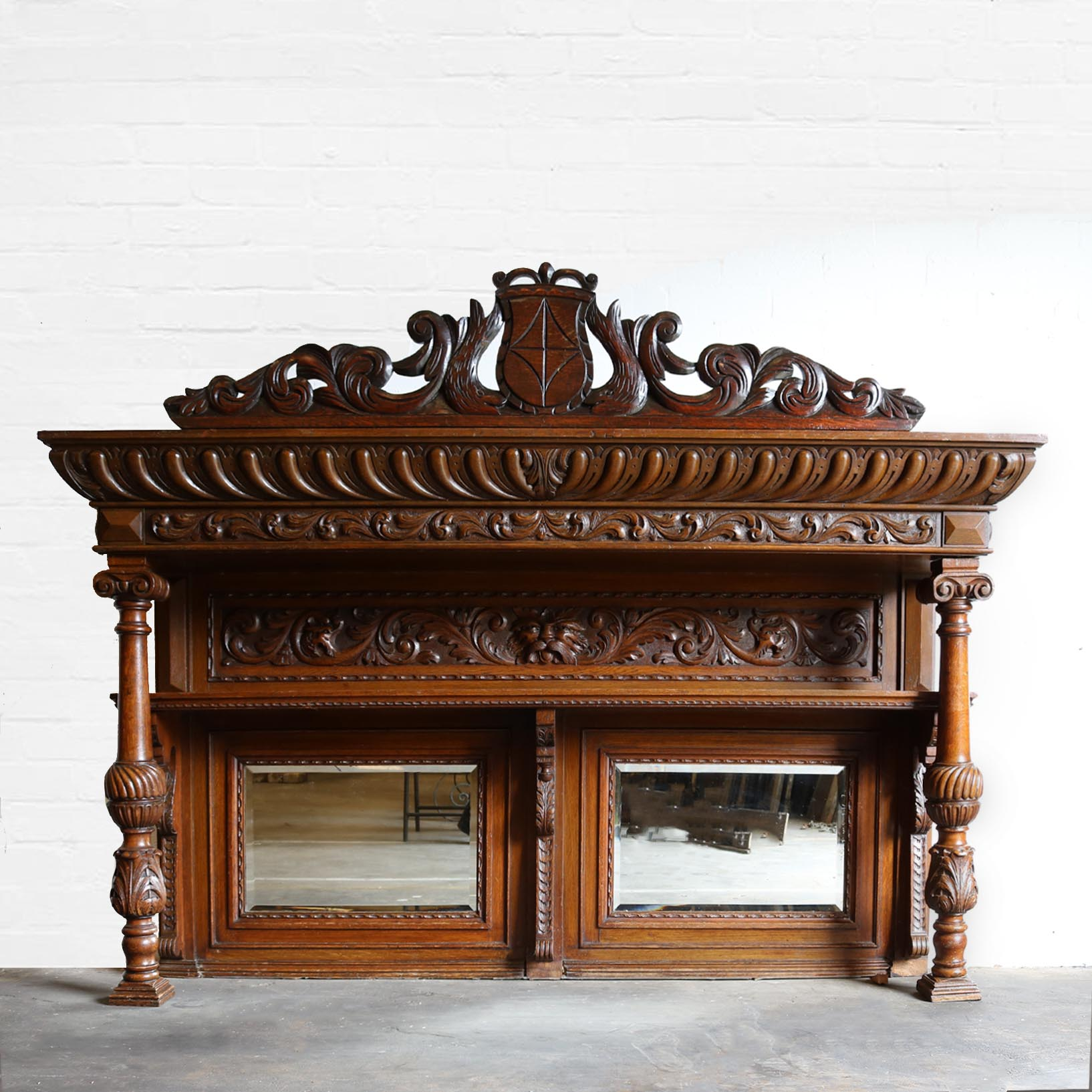 An ornately carved over mantel with shelf and bevelled mirrors
