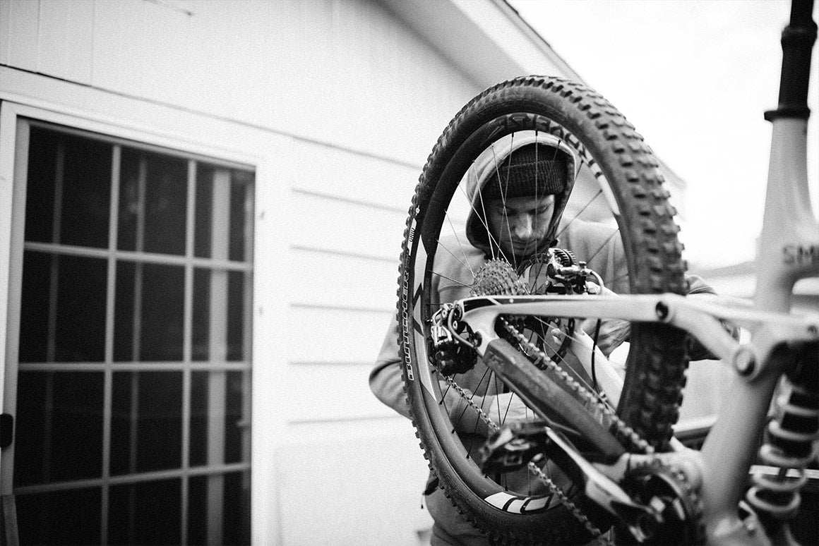 Black and white dramatic image of man adjusting bike wheel