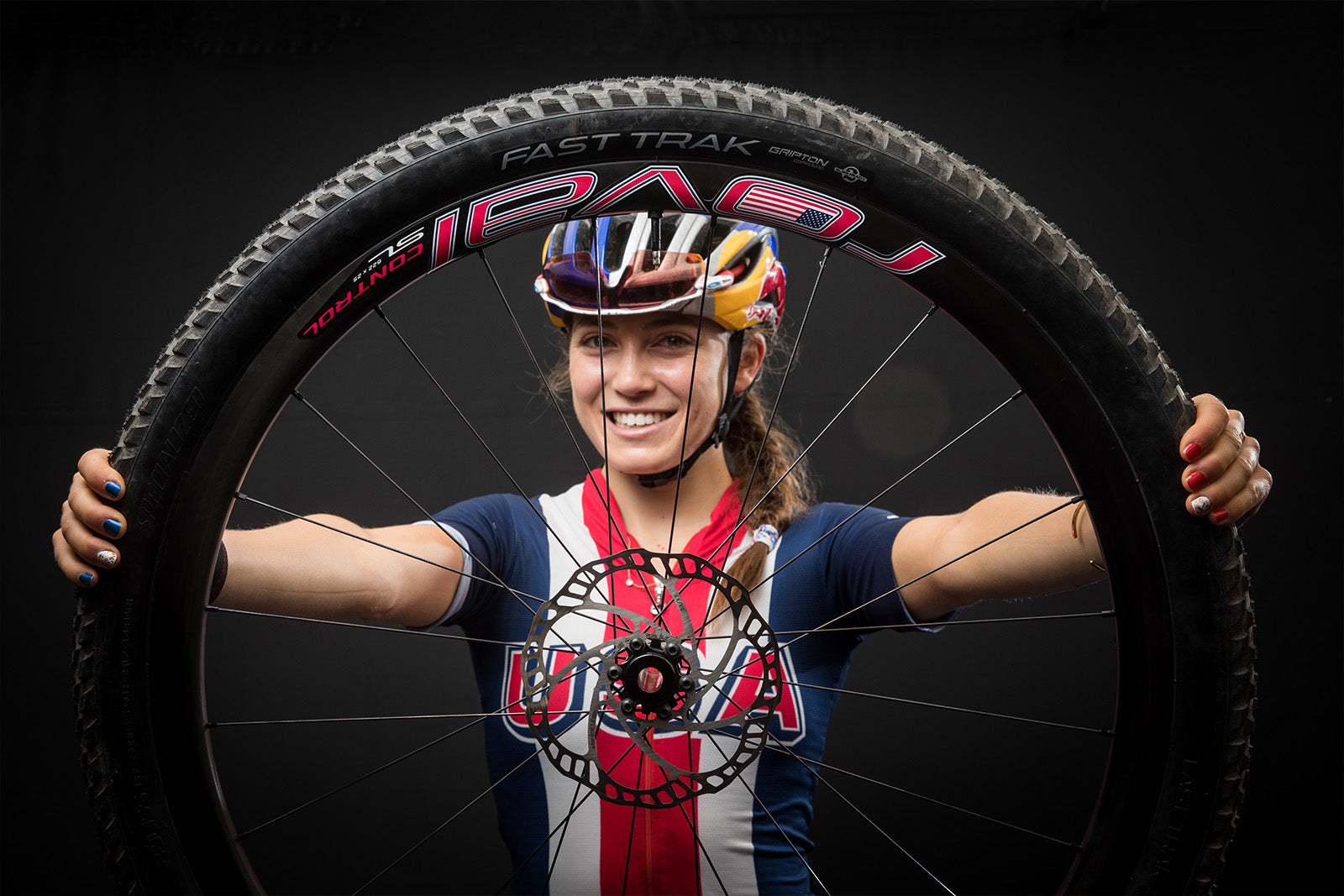 USA female cyclist holding Roval wheel in front of face