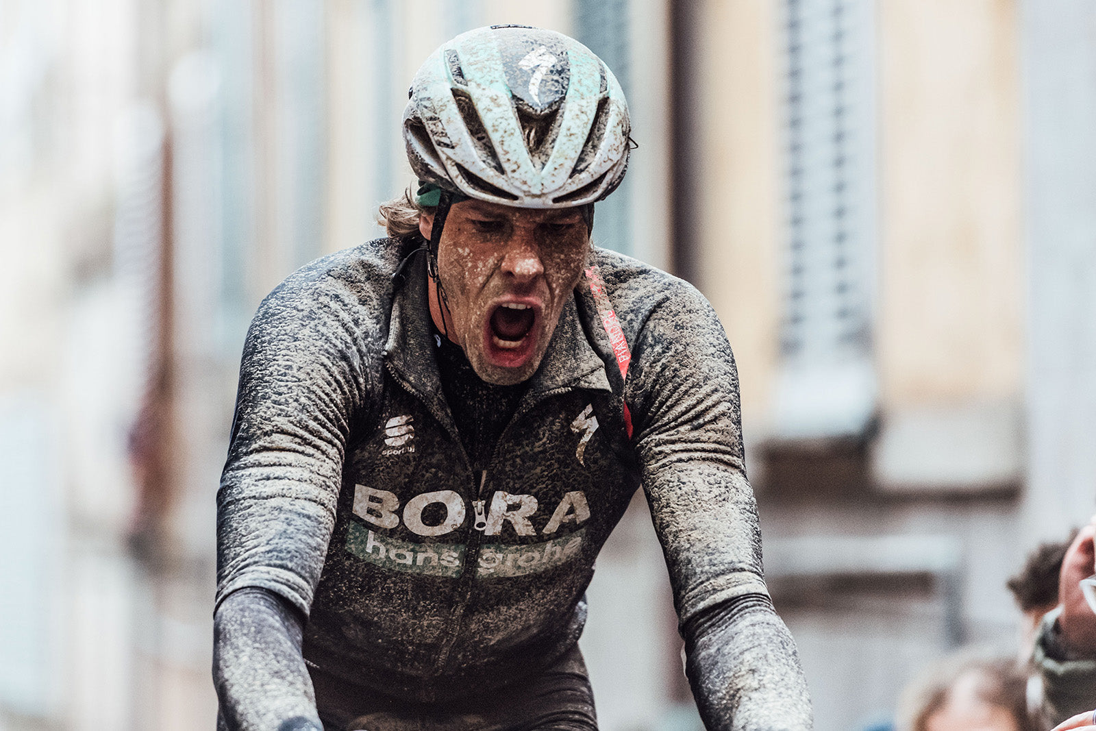 Male rider shouting during race with mud all over himself