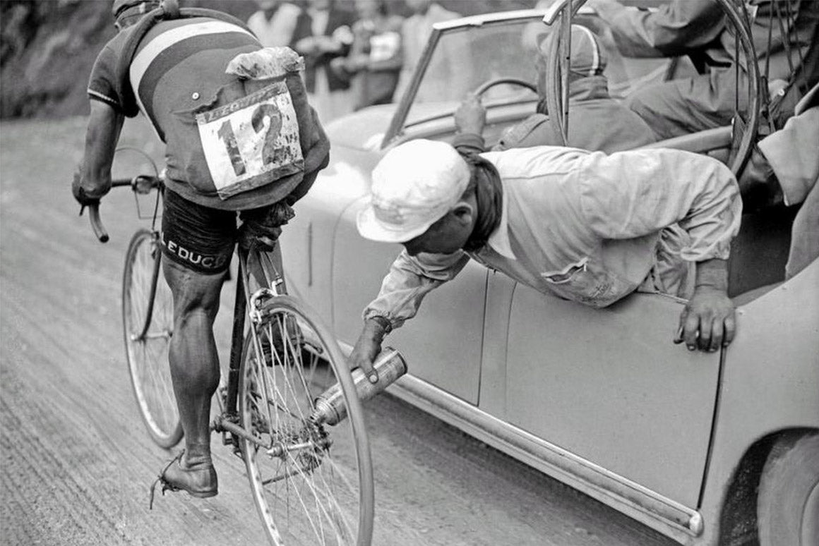 Historical image of man fixing a rider's bike from the car door