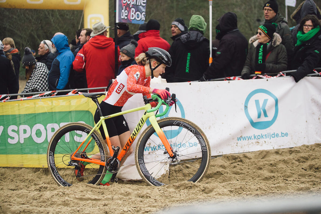 Maghalie Rochette walking bike through mud in front of race spectators