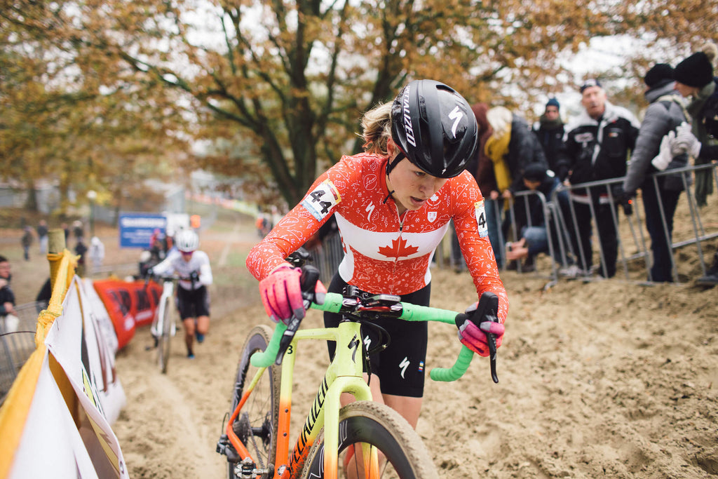 Maghalie Rochette walking bike through mud during race