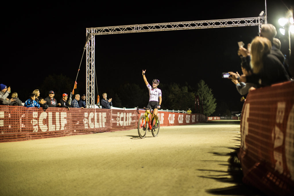 Maghalie Rochette cheering while crossing the finish line at night