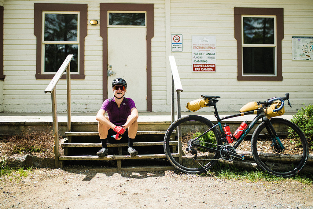 Maghalie sitting on a porch of small cabin next to her bike