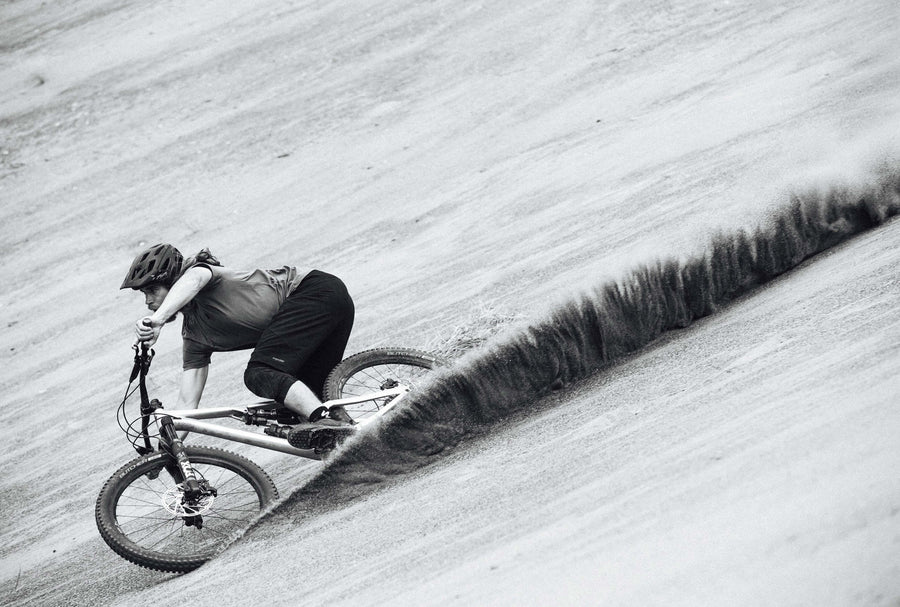 Black and white image of male cyclist speeding