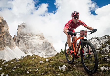 Male cyclist riding cross country with mountains in background