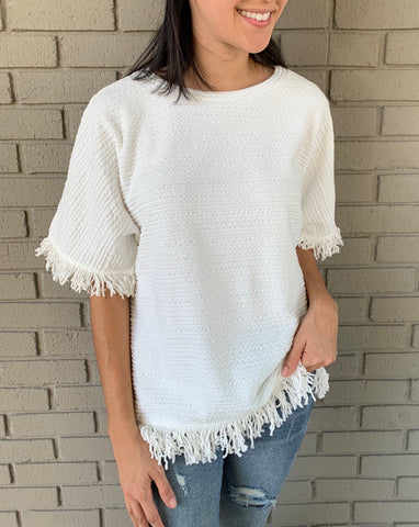 white blouse with fringe accents