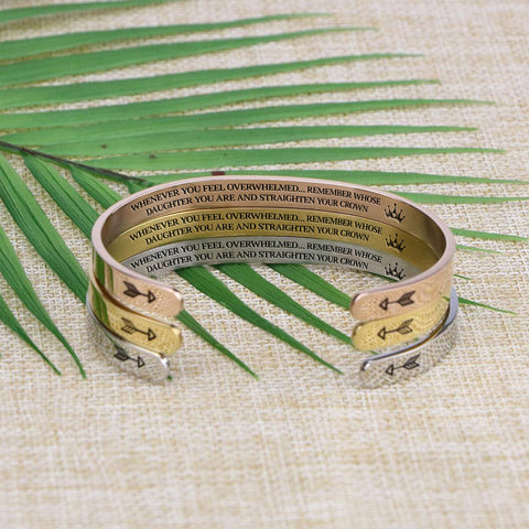 Straighten Your Crown bracelets in silver, gold, and rose gold stacked on a burlap background.