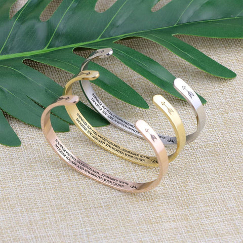 Straighten Your Crown bracelets in silver, gold, and rose gold standing on a burlap background.