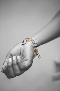 Woman's wrist with layered bangles and a sapphire-colored gemstone charm.