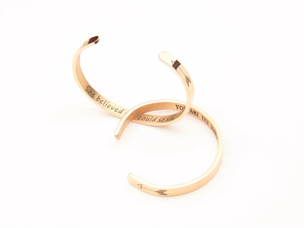Gold bracelets with inspiring messages on a white background.