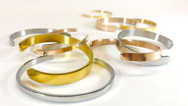 Various cuff bracelets, bangles and bands in silver, gold and rose gold.