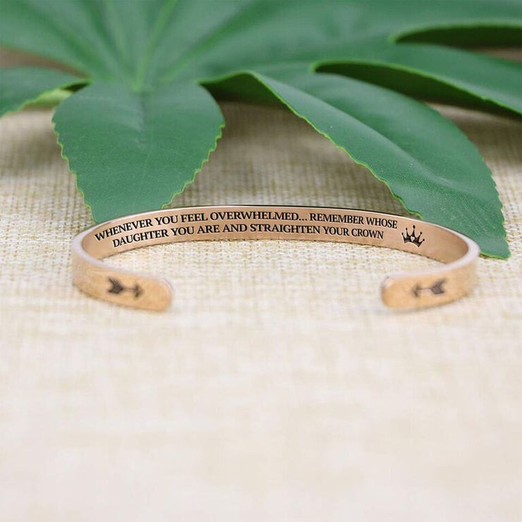 Straighten your crown bracelet with rose gold plating with message in focus on a burlap surface with a leafy background
