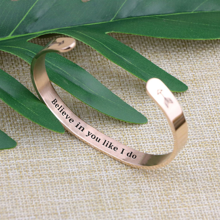 Believe in you like I do bracelet with rose gold plating standing on a burlap surface with a leafy background