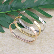 Straighten your crown bracelets with silver, gold, and rose gold plating standing on a burlap surface with a leafy background.