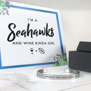 I'm a Seahawks and wine kinda girl bracelet in silver with a gift box, bag, and card in the background