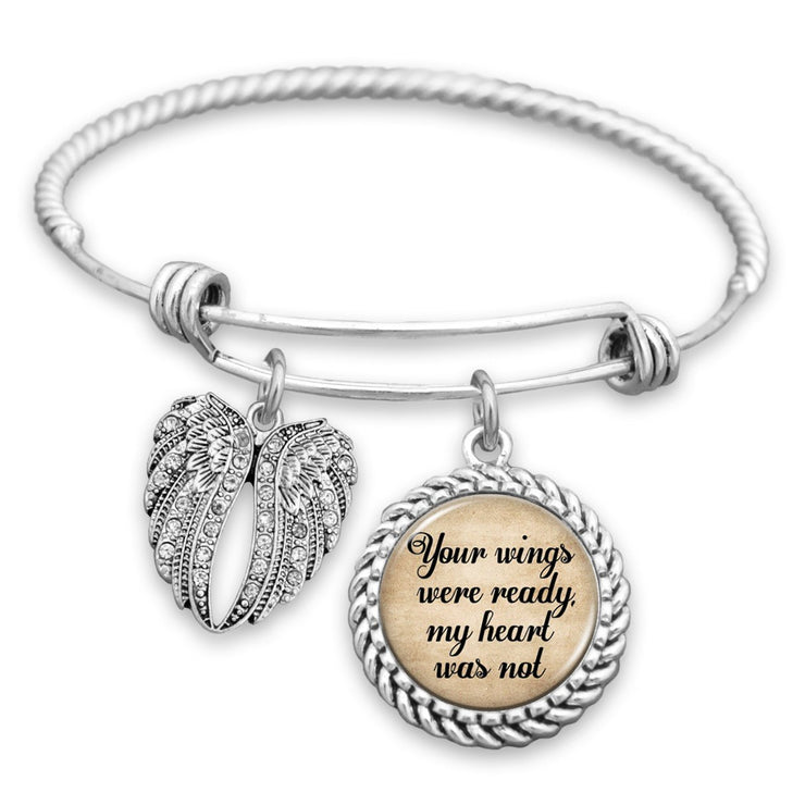 I am so proud of you bracelet with silver plating with arrows in focus on a burlap surface with a leafy background