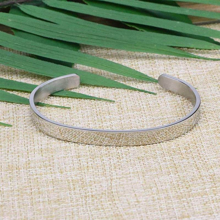 Outer view of the straighten your crown bracelet with silver plating laying flat on a burlap surface with a leafy background.