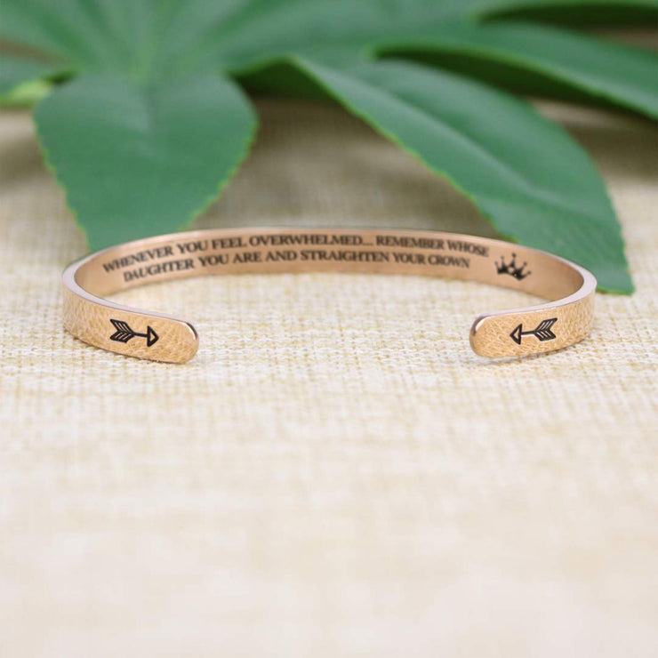 Straighten your crown bracelet with rose gold plating with arrows in focus on a burlap surface with a leafy background