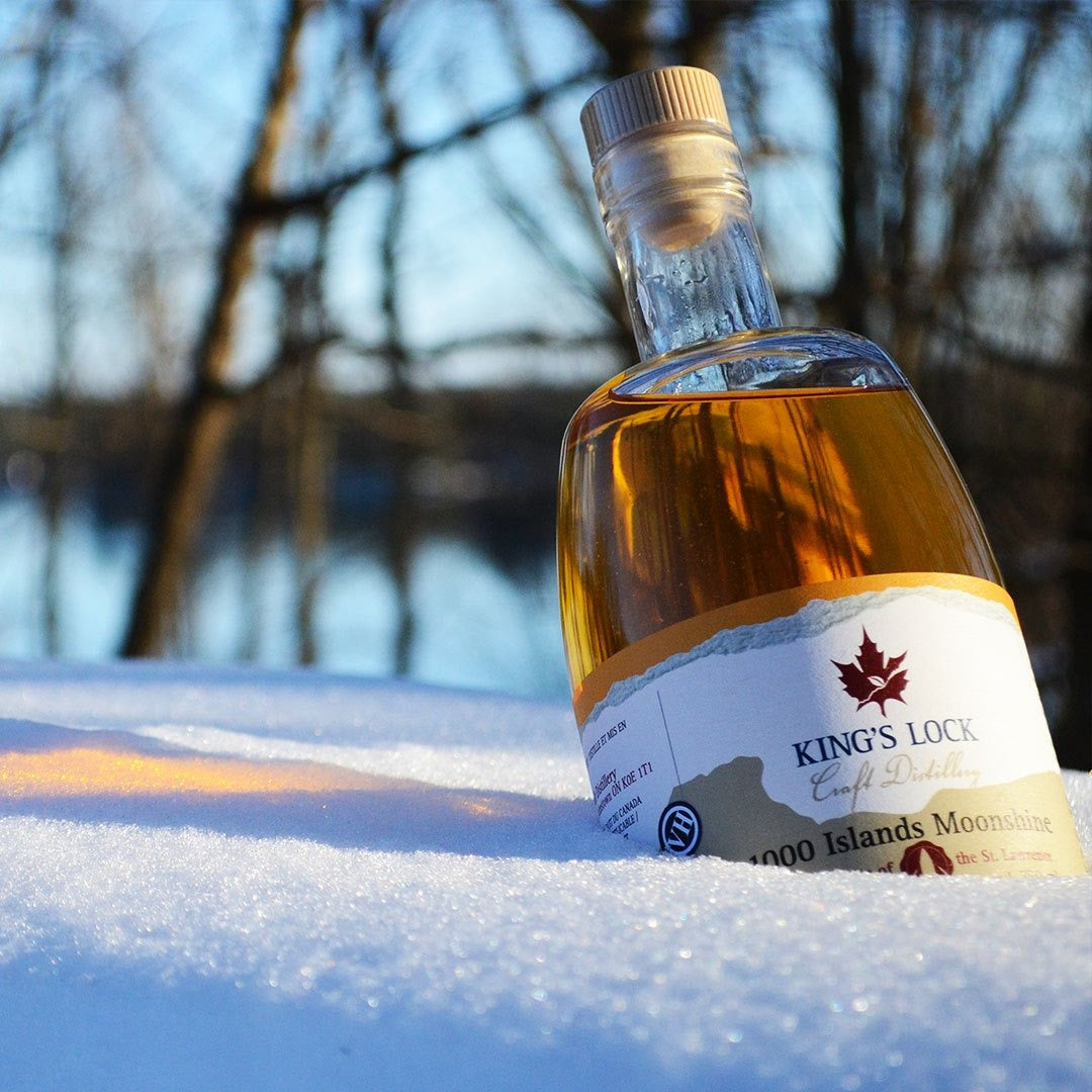 A close up view of 1000 islands moonshine bottle placed in the snow