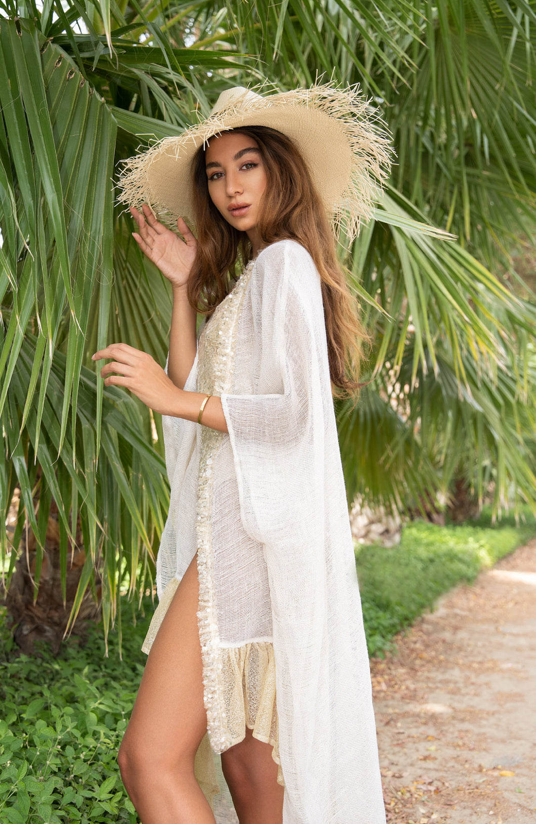 Gold foiled linen poncho with ruffled bottom detail and sequin embellished trims. The perfect summer piece. Use it as a coverup to glam up your swimwear. Paired with the Nia body swimsuit for a glamorous look. Luxury Resort wear. Worldwide Shipping.