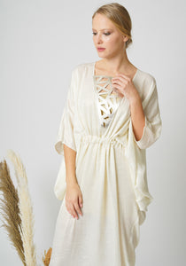 Mykonos Kaftan Dress in Pearl - half-body image. Crafted from shimmery silky fine viscose. The kaftan features butterfly sleeves with a gold leather laser cut V-neckline. It can be tightened around the waist or worn loose for a relaxed look. Perfect for elegant celebrations or resort destinations. Worldwide Shipping Available.