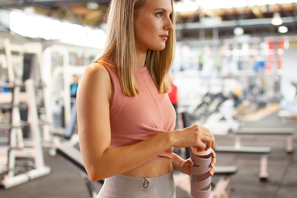Image of Bellbeat co-founder Urska looking determined at the gym after drinking water from her Spring smart bottle