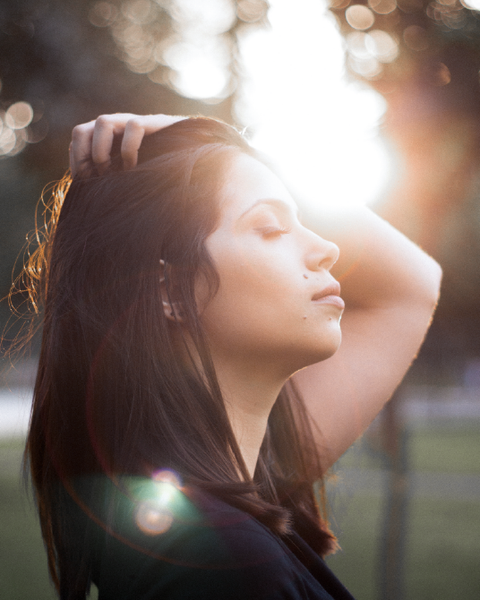 Image of woman with closed eyes enjoying the sun