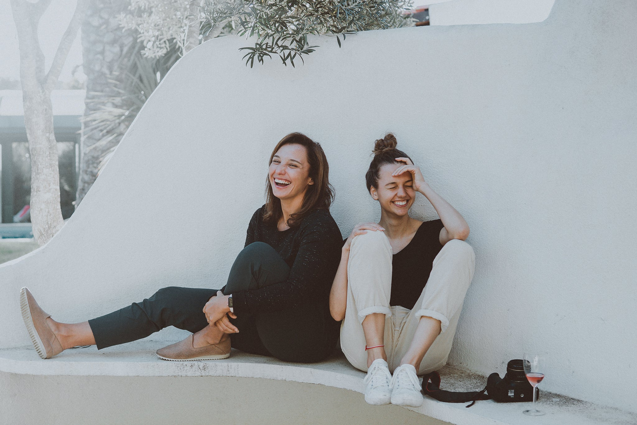 Image of two friends sitting outside and laughing together