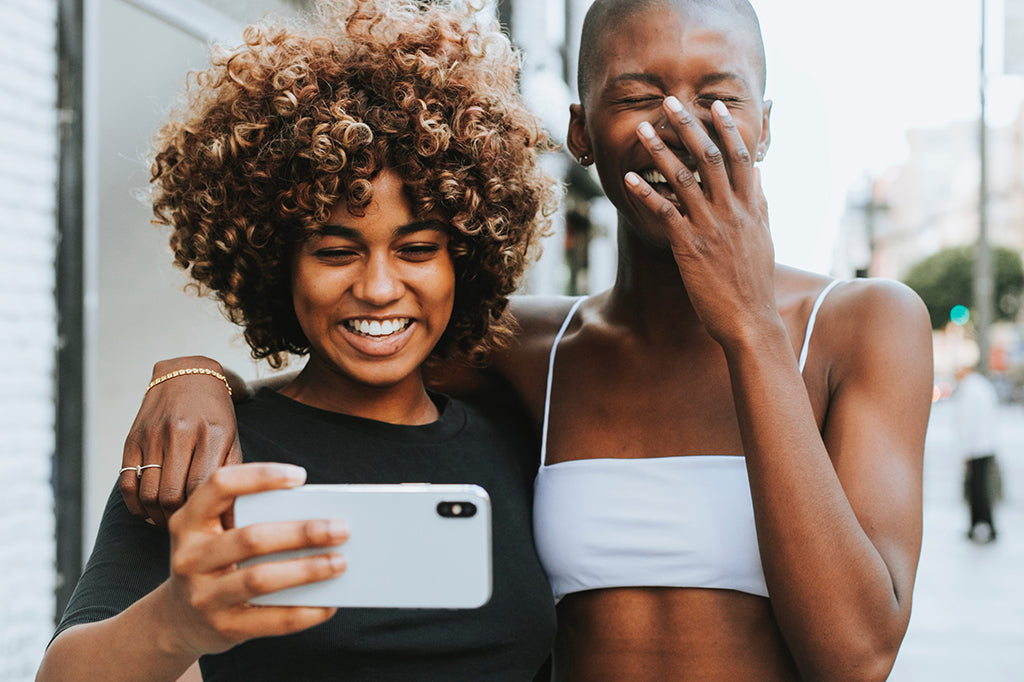 Image of two friends taking a picture with their phone and laughing