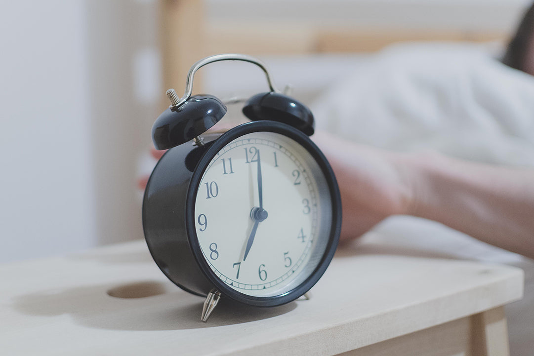 image of an alarm clock and someone pushing the snooze button