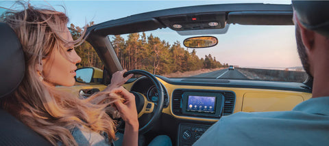 Couple in a car driving with Sony Stereo