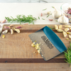 Taste of Home Bench Scraper with Sea Green handle, angled view on cutting board, angled view, lifestyle background