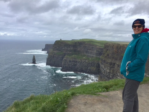 Moher cliffs, hiker wearing Wild Kiwi clothing storm jacket from wildkiwiclothing.co.nz