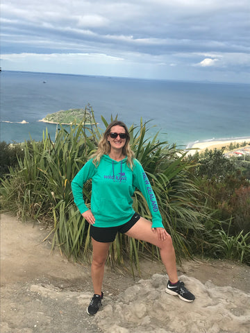 Jogger at the top of Mount Maunganui, New Zealand, wearing Wild Kiwi clothing lightweight hoodie.