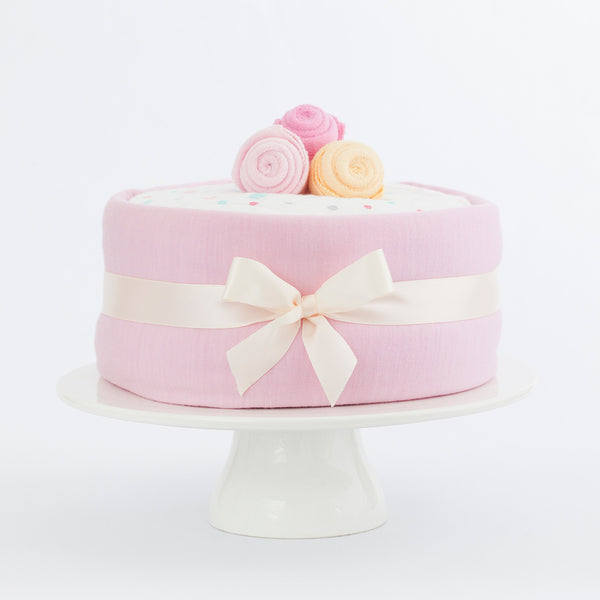 Merino nappy cake for a baby girl with pink, our ingredients include: Made in New Zealand Lambino Merino wrap, bodysuit and beanie, Treasures nappies and more, perfect newborn gift for a baby shower.