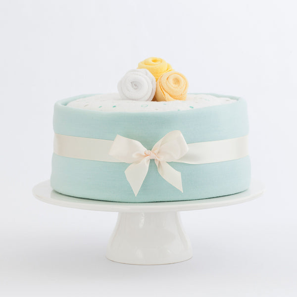 Merino nappy cake- Sweet Mint, Ingredients include: Lambino Merino wrap, bodysuit and beanie, Lambino Merino made in New Zealand, Treasures nappies and more, perfect newborn gift for a baby shower.