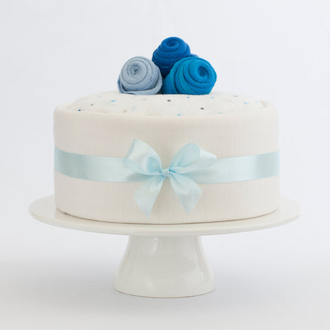 Merino nappy cake for a baby boy in blue, our Merino clothing is made in New Zealand. Ingredients include: Merino infinity nursing scarf/breast feeding scarf, Merino bodysuit and beanie, Treasures nappies and more. Perfect newborn gift for a baby shower.