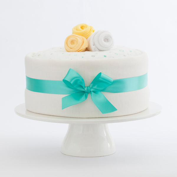 Merino nappy cake for a neutral baby gift, our ingredients include: Made in New Zealand Lambino Merino wrap, bodysuit and beanie, Treasures nappies and more, perfect newborn gift for a baby shower.