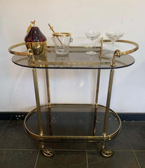 1960S ITALIAN MIDCENTURY BAR CART WITH SMOKED GLASS SHELVES AND BRASS HANDLES