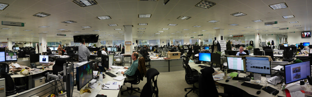 large newspaper newsroom with workers at their desks