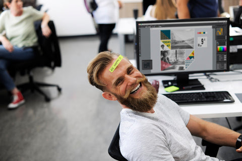 office worker laughing by his computer