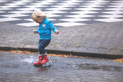 small child splashing in a puddle