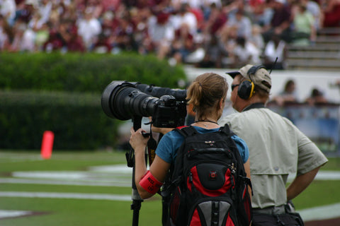 female photographer with a big lens on the sidelines