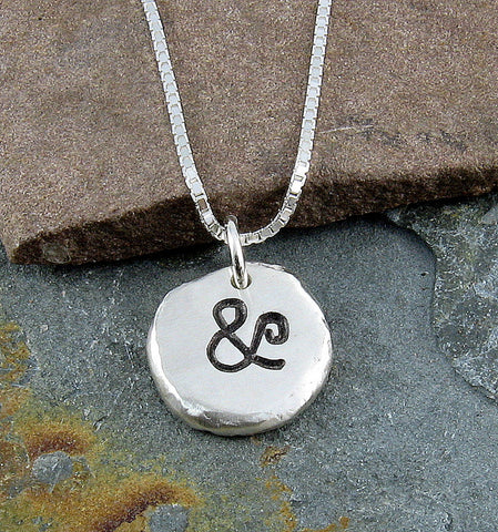 Ampersand necklace designed using recycled silver and a hydraulic press.