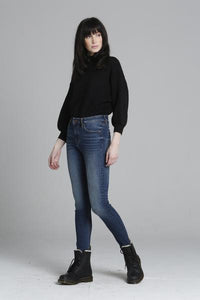 An image of a woman wearing the Ace High Rise denim skinny jeans from Vigoss with dark boots.