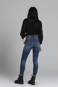 A back view image of a woman wearing the Ace High Rise denim skinny jeans from Vigoss.