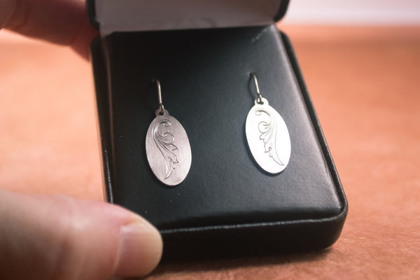 Hand-engraved titanium earrings by Podforge in a black leatherette gift box